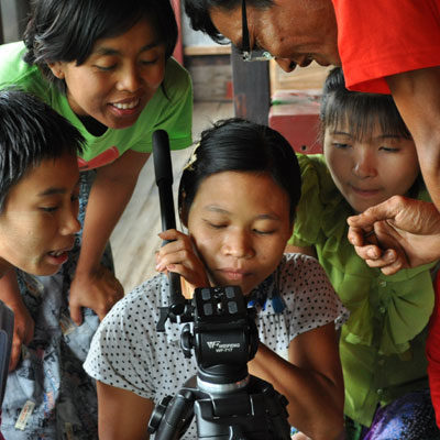 A group learn to use a tripod during a Participatory Video project in Myanmar (Burma)