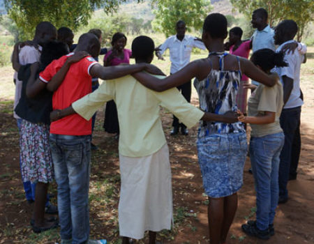 A group of participants in Uganda stand in a circle with arms around one another