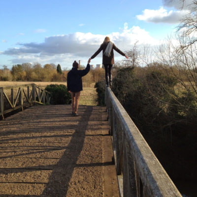 A woman walks along the railing of a bridge whilst her hand is held by a friend