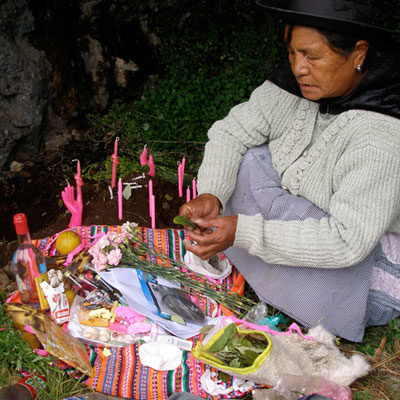 An indigenous Yaqui woman makes an offering and blessing in the high Andes, Peru