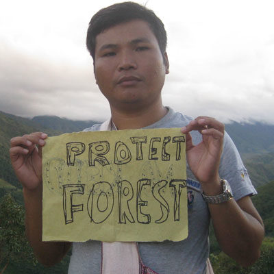 An indigenous activist from Bangladesh holds a sign saying 'Protect Forest'