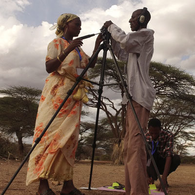 A woman and a man in Northern Kenya attach a camera to a tripod during a Participatory Video project
