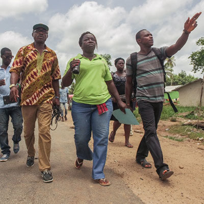A group of people in Liberia walking down the road holding camera equipment during a Participatory Video project