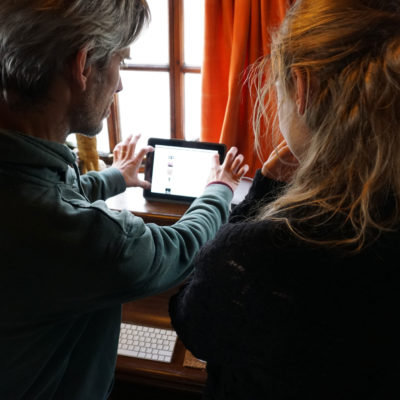 A man and a woman looking at a computer used for editing Participatory Video