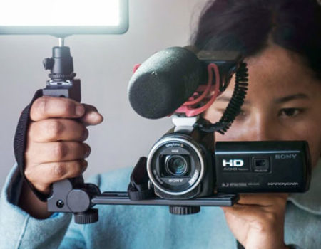 A young indigenous woman from North-East India holds a video camera