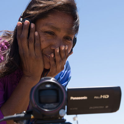 An indigenous Yaqui woman looks at the image on a video camera