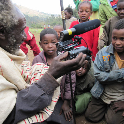An Ethiopian elder from the Gamo Highlands uses a video camera to record local children gathered around him
