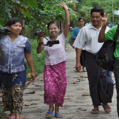 A group of participants carry their camera through a village in Myanmar