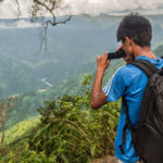 An indigenous Khasi youth films the lush green hillsides in north-east India