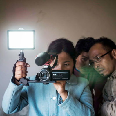 Indigenous Garo youth holding a camera and lights whilst making their Participatory Video