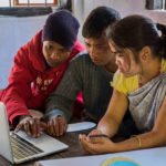 Indigenous Khasi youth editing their Participatory Videos on a laptop