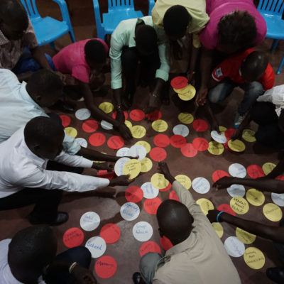 A group sort cards during a Participatory Video monitoring and evaluation exercise in Uganda