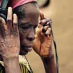 A widow in northern Ghana listening to the footage they record through headphones