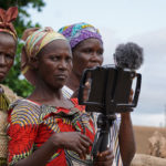 Three widows in Ghana holding a camera during a Participatory Video on land and corruption