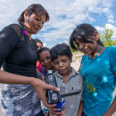 A woman shows children the video they recorded on the camera, during a Participatory Video project in Mexico